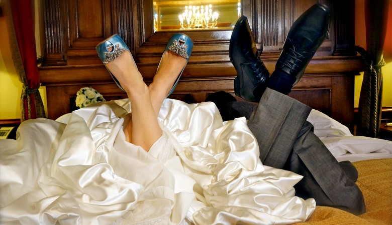 Bride and groom lying on the marital bed