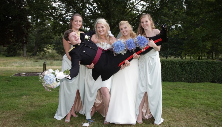 Bridesmaids holding the groom